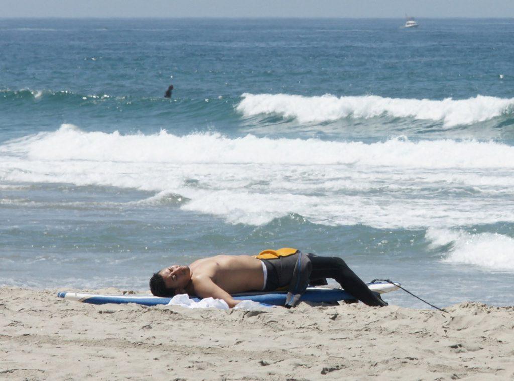 Sleep on your surfboard on the sand.