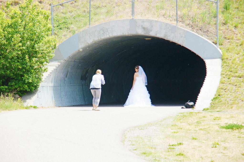 A bride poses in a pedestrian tunnel.