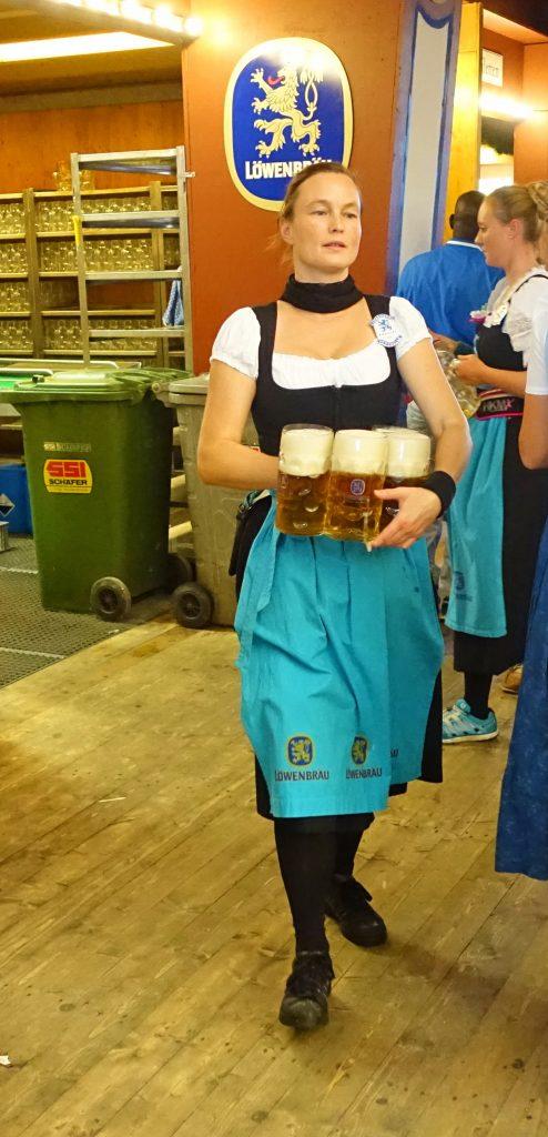 A Kellnerin serving four Maßkrug.