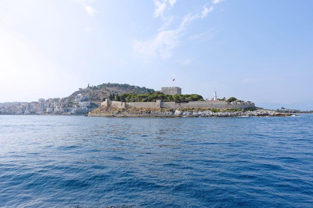 Güvercinada as seen from the ferry, with Kuşadası in the background.