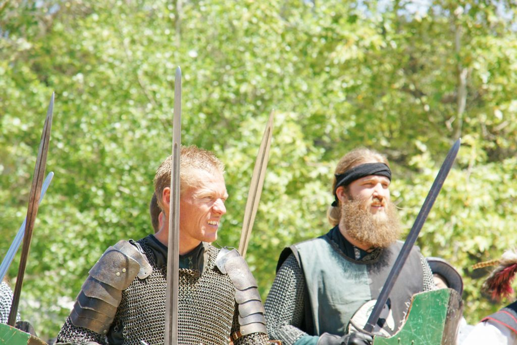 Knights clad in maille and iron glare at enemy forces.