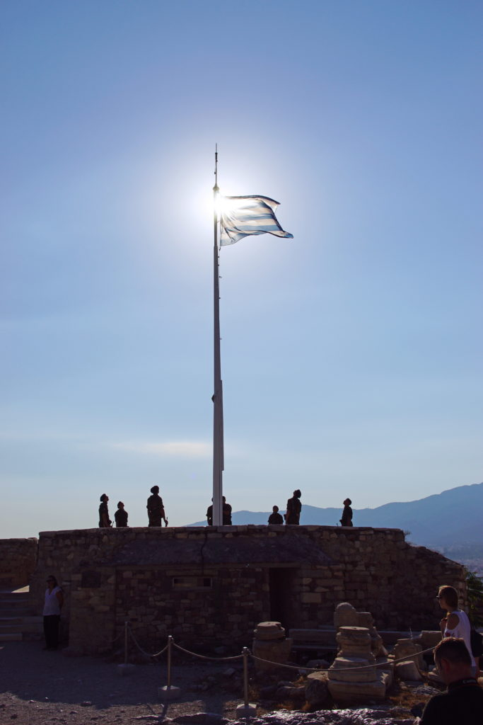 The Greek flag extends under the morning sun.