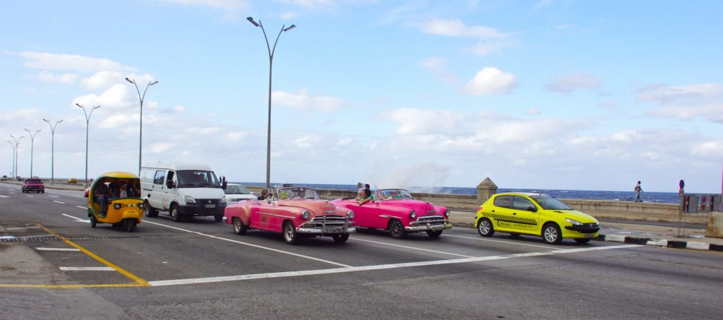 Cubans in colorful cars commuting.